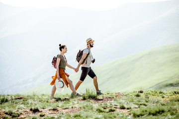 Beautiful couple walking with backpacks on the green meadow, while traveling in the mountains during the summer time Fototapete