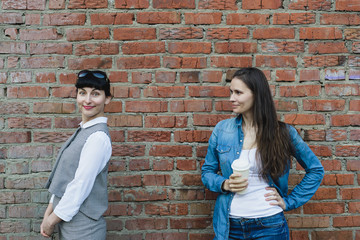 two caucasian women girlfriends stand near old grange red brick wall background in office and casual clothes, posing on outdoors, horizontal stock photo image