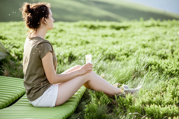 Woman applying sunscreen lotion while sitting at the campsite, traveling in the mountains