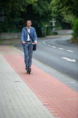 Mann fährt mit Elektroroller in der Stadt auf Radweg