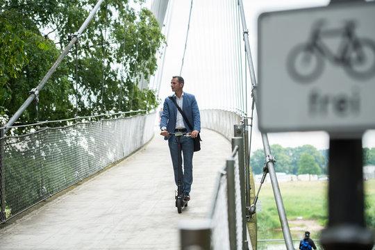 Mann mit Anzug und Elektroroller auf Brücke