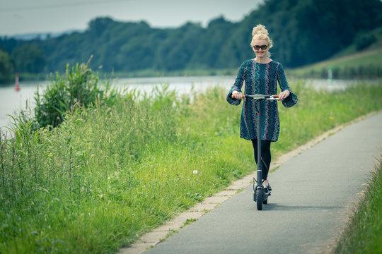 Frau macht Ausflug mit Elektroroller entlang Fluß auf Radweg