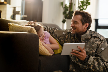 Happy soldier and his small daughter using touchpad at home.
