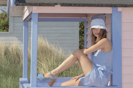 Scandinavian Girl with blue suit, wave bucket hat and blue shoes sitting in a beach house