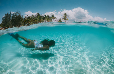 Beautiful woman swimming underwater in a tropical sea full of corals. under water shot with action camera. concept about wanderlust travels Wall mural