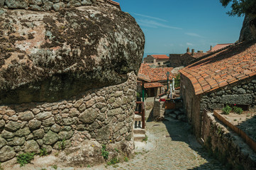 Old houses and stone wall with big rock in Monsanto