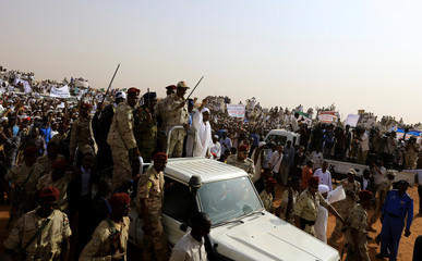 Lieutenant General Mohamed Hamdan Dagalo greets his supporters as he arrives at a meeting in Aprag village
