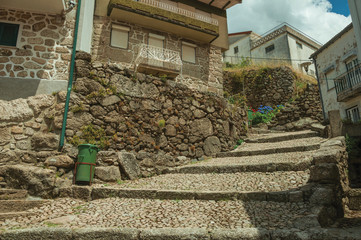 Old stone houses in cobblestone alley on slope with steps