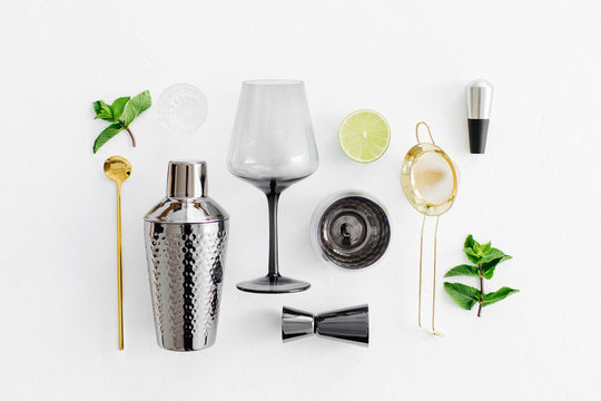 Set of bar accessories for cocktail making. Shaker, jigger, glass, spoon  and  other bar tools with lime and mint leaves on withe  background.
