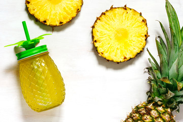 Pineapple juice and slices of fresh pineapple, top view, copy space