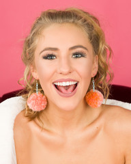 Closeup of expressive, happy and beautiful young blonde woman wearing fuzzy pompom earrings
