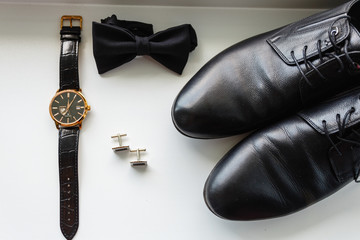 Composition of men's accessories. Expensive wristwatch, black classic butterfly, stylish cufflinks, leather classic shoes top view.