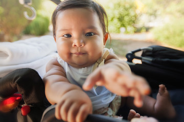 A cute baby using her hands to reach for something infront of her while riding on a carriage type of stroller.