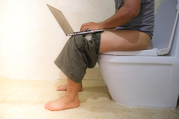 Using a laptop computer on a toilet. The Asian man sitting in the toilet and working at the laptop. Royalty high-quality free stock photo image of a man working on his computer while on the toilet