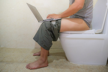 Using laptop computer on toilet or restroom. The Asian man sitting in the toilet and working on the laptop. Royalty high-quality free stock photo image of a man working on computer while on the toilet