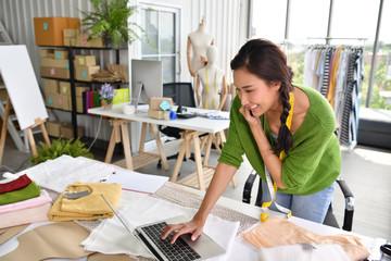 Young Asian woman entrepreneur / fashion designer working in studio