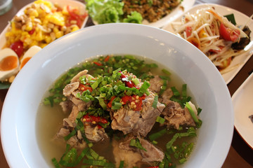 Above view of a bowl of spicy Asian pork rib soup with a background of various other traditional dishes.
