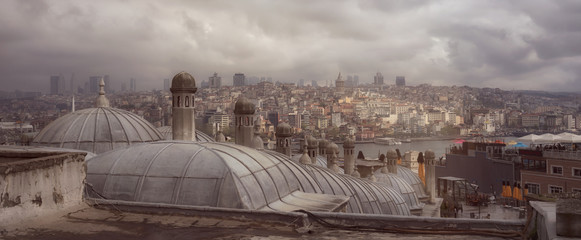 Istanbul cityscape in a cloudy day, view on the Bosphorus and Galata tower from the roofs.