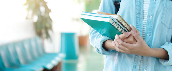 Student girl holding books and carry school bag while walking in school campus background,...