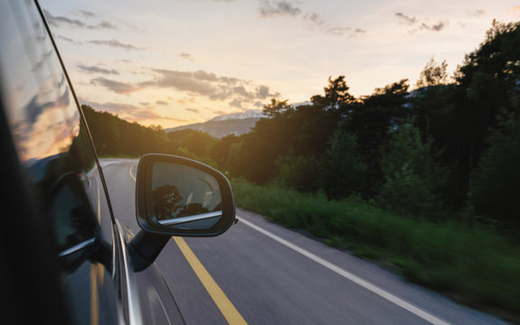 Driving on country road in summer at sunset, side wing mirror view