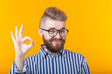 Handsome young man with a mustache and a beard with glasses shows ok posing on a yellow background....