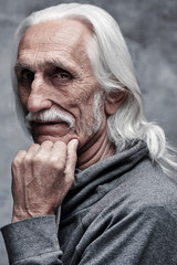 Aged gray haired Caucasian retired man thinking about life. Grandfather in glasses with mustache and thoughtful facial expression holds his chin