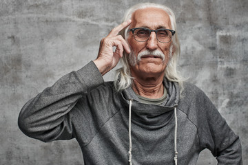 Aged gray haired Caucasian male pensioner thinks diligently, holding fingers at temples. Grandfather in glasses with mustache trying to concentrate, brainstorming, encourages to think well
