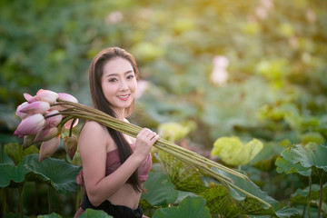 Woman holding lotus with traditional dressing in garden