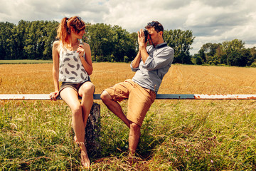 Photographer taking picture of a beautiful woman in a countryside landscape