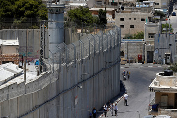 People walk past a section of the Israeli barrier in Bethlehem, in the Israeli-occupied West Bank