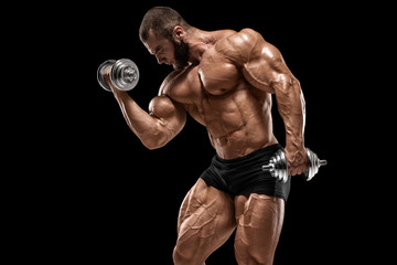 Muscular man doing exercises for biceps isolated on the black background. Strong male naked torso abs