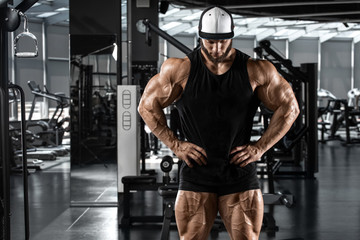 Muscular man showing muscles in gym, workout. Strong bodybuilding male Wall mural