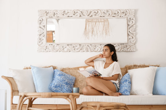 Dreamy attractive young tanned woman traveler relaxing after tourist trip sit hotel room sofa contemplating window view thinking. Girl lying couch reading book drink coffee in hygge house