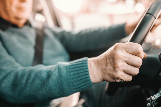 Close up of senior man holding hands on steering while and driving his car.