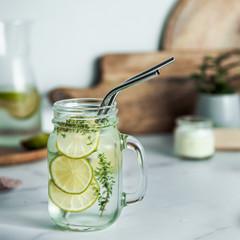 Fototapeta Cold drink in mason jar with metal straws on kitchen table. Lemonade or detox water with lime and thyme in glass jar wit metal straw indoor. Recyclable straws, zero waste concept obraz