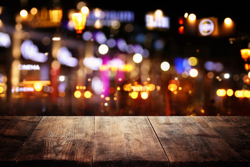 background of wooden table in front of abstract blurred restaurant lights