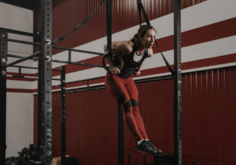 Young crossfit woman doing muscle-ups on gymnastic rings at the gym.