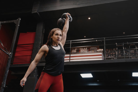 Strong crossfit woman exercising with a kettlebell at the gym. Female doing functional training