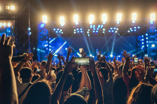 Concert crowd of Music fanclub hand using cellphone taking video record or Live stream with superstar songer, happy new year, christmas and festival concept