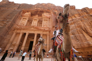 Tourists ride camels and take pictures in front of the treasury site in the ancient city of Petra, south of Amman