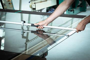 Obraz A worker cuts glass in a glass workshop - fototapety do salonu