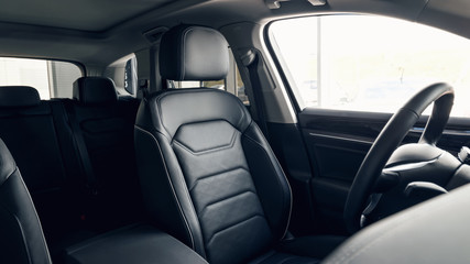 Black leather car interior. Modern car interior dashboard and steering wheel. Modern luxury car black perforated leather interior. Interior details