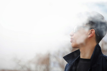 Asian young man smoking on the street