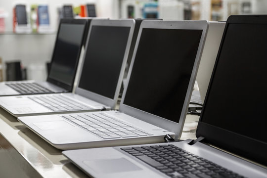 A row of laptops in computer shop. Closeup, selective focus