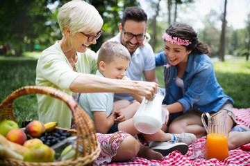 Happy family enjoying picnic in nature at summer