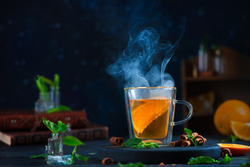 Printed roller blinds Tea Double wall glass cup with citrus tea, cinnamon, and mint leaves. Steam in dark food photography with copy space.
