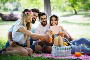 Group of young people taking a selfie outdoors, having fun