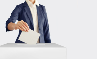 Voting. Woman putting a ballot into a voting box.