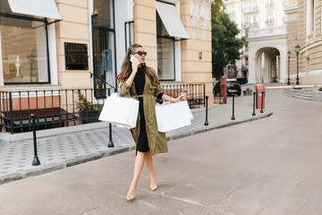 Outdoor portrait of busy elegant woman in trendy high heel shoes talking on phone on the street and looking around. Pretty hispanic lady with purchases hurrying home in weekend. Wall mural