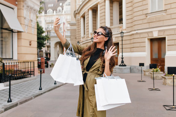 Graceful fashionista girl wears green coat making selfie on the street. Attractive brunette woman with packages from boutique taking picture of herself.